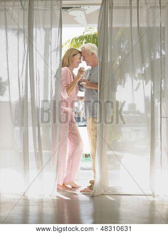 Vista lateral de longitud completa de una media de edad flautas tostado champagne de pareja detrás de la cortina
