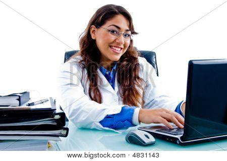 Cheerful Female Doctor Working On Laptop