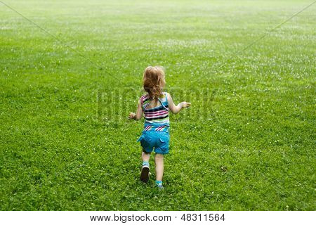 Young child running through a meadow
