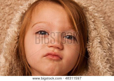 Young child puckering lips under fur cover