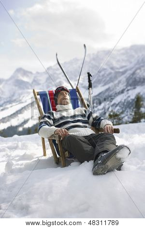 Man in warm clothing resting on deckchair in snowy mountains