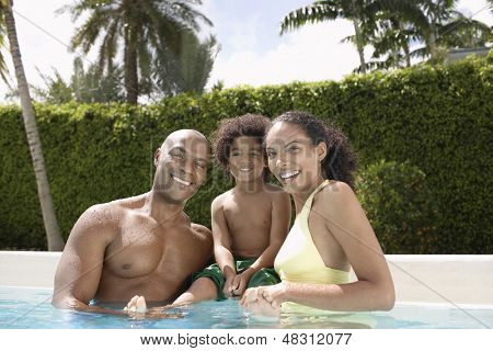 Portrait of happy African American parents with son in swimming pool