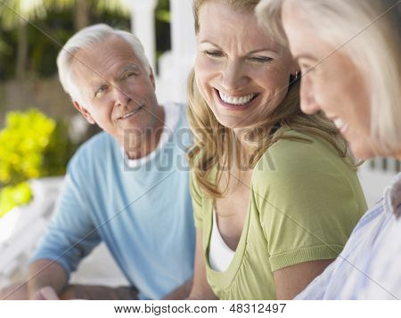Closeup of mature man with two cheerful middle aged women sitting on verandah