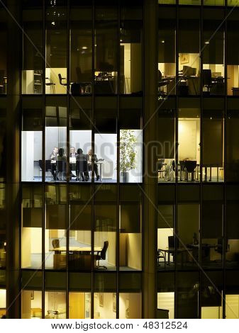 Business meeting viewed through illuminated window of office block at night