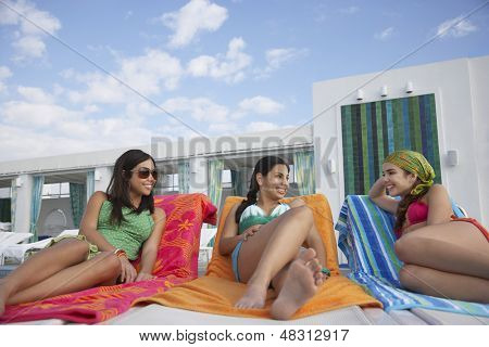 Three teenage girls lying on sunloungers at resort