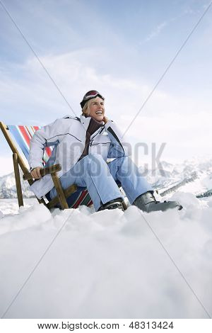 Low angle view of a smiling woman sitting on deckchair in snowy mountains