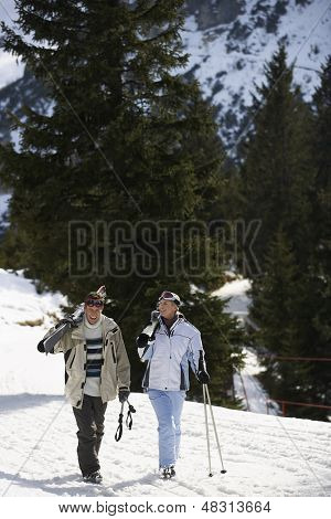 Full length of a skiing couple carrying skis on shoulders on ski slope