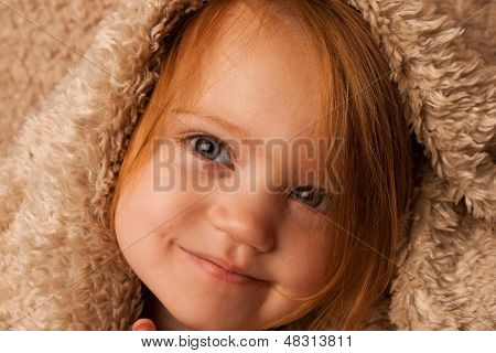 Small child smirking with blanket