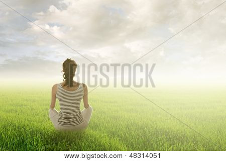 Woman of brunet hair sit on grassland against sunrise or sunset, concept of leisure, lifestyle, healthy, zen etc with good copyspace on heaven.