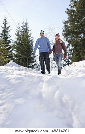 Full length low angle view of a couple descending snow covered hill