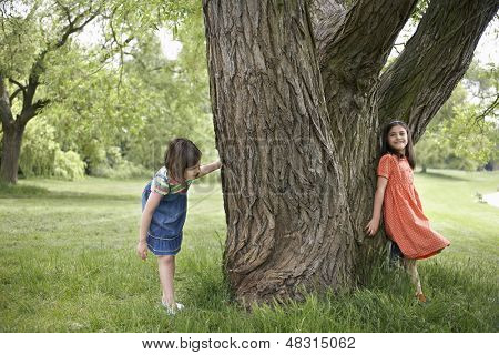 Full length of two girls playing hide and seek by tree