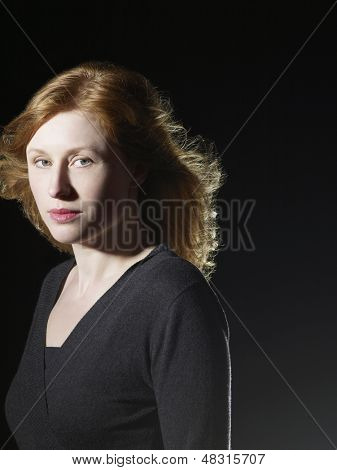 Closeup of beautiful woman with windswept hair looking at camera on black background