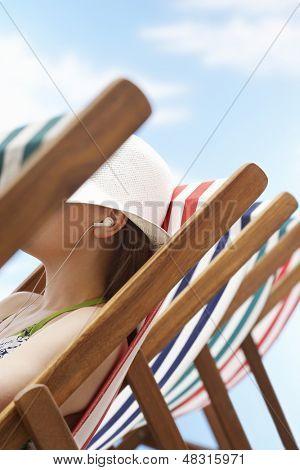 Closeup of woman listening music through earphones on deckchair at beach