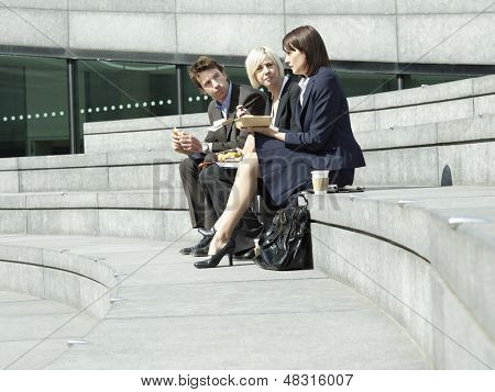 Full length of three business people having lunch on steps outdoors