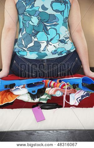 Midsection of woman sitting on overstuffed suitcase in bed