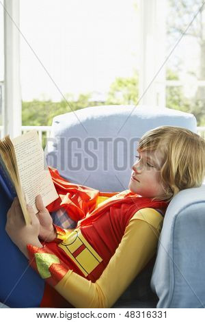 Side view of a young boy in costume reading book indoors
