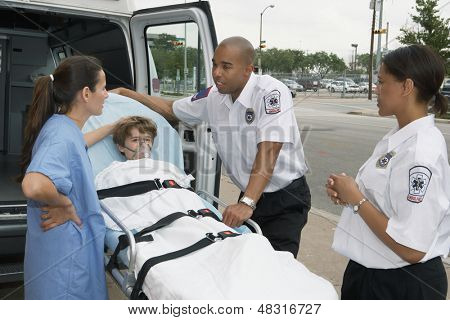 Female doctor standing next to a boy on gurney
