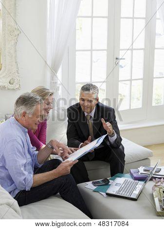 Mature couple sitting on sofa with financial advisor