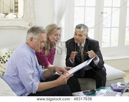 Pareja sentada en el sofá con un asesor financiero