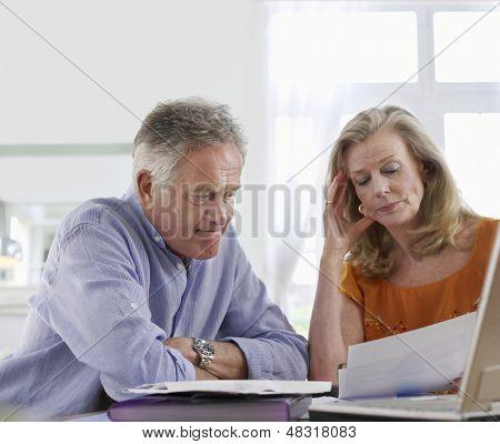 Pareja preocupada con facturas sentado en la mesa de comedor en la casa