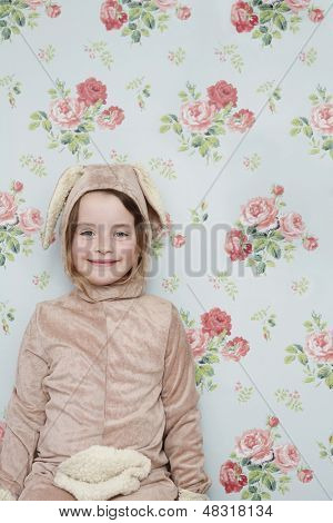 Portrait of a cute young girl in bunny costume against wallpaper with floral pattern