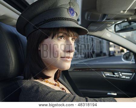 Closeup of female chauffeur in uniform driving a car