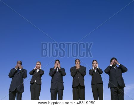 "Businesspeople outdoors motioning ""hear no evil, see no evil, speak no evil"""