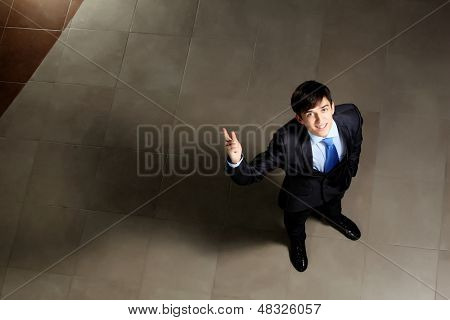 Image of young businessman pointing with his finger up. Top view