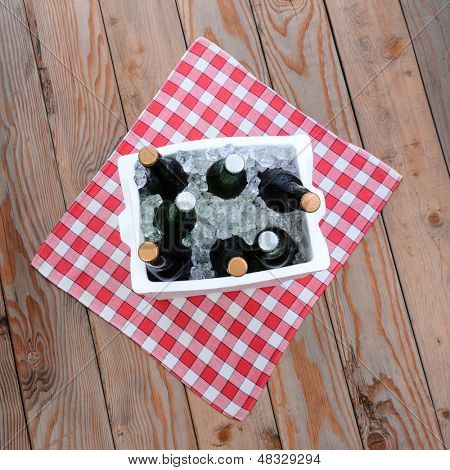 Overhead shot of a styrofoam ice chest full of beer bottles on a red and white checked table cloth on a wood deck. Square Format.