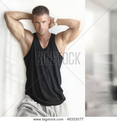 Portrait of sexy muscle man posing in modern studio