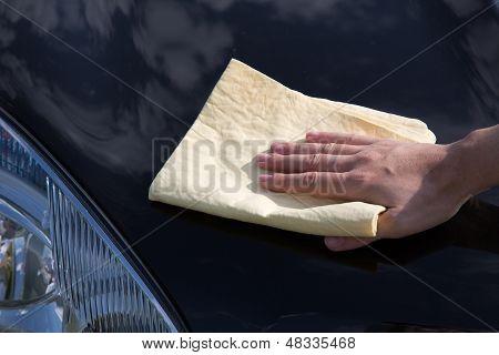 Polishing The Hood Of A Car With A Chamois