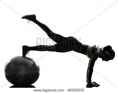 una mujer ejerciendo posición de tablón de entrenamiento fitness en la bola de la aptitud en silueta en blanco centrico