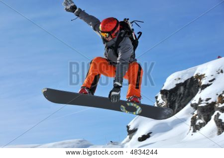 Snowboarder In Red Performing A Jump