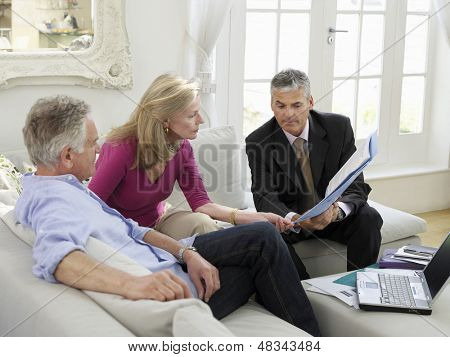 Mature couple sitting on sofa with financial advisor