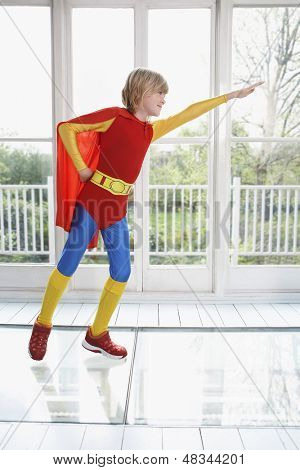 Full length of a young boy in superhero costume with arm extended indoors