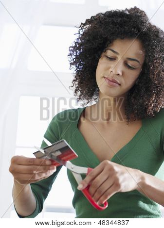 Young mixed race woman cutting credit card against white background