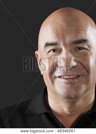 Closeup portrait of bald middle aged man smiling on black background