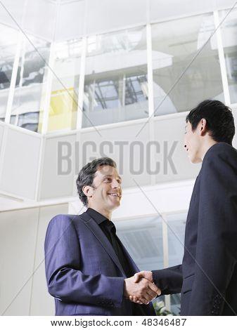 Low Angle View of zwei Geschäftsleute Händeschütteln im Büro atrium