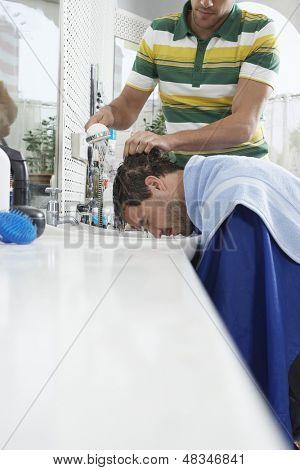 Man getting hairwash by hairdresser in hair salon