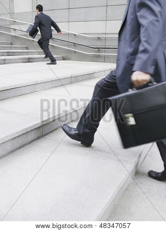 Side view of a businessman running on stairs with cropped man in foreground