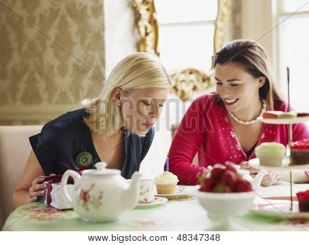 Young woman blowing candle on cupcake by friend at dining table