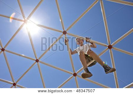 boy playing on high up on playground, view from ground toward sun
