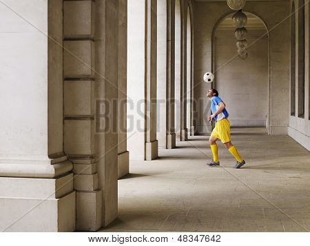 Full length of a soccer player bouncing ball Off head in portico