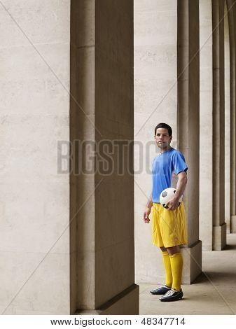 Volle Länge-Porträt eines Fußballspielers holding Ball im Portikus