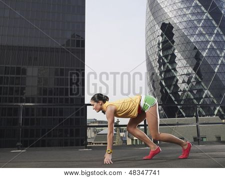 Full length side view of female runner in start position against downtown buildings in London