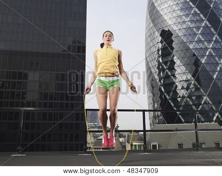 Low angle view of a young woman skipping against downtown buildings in London