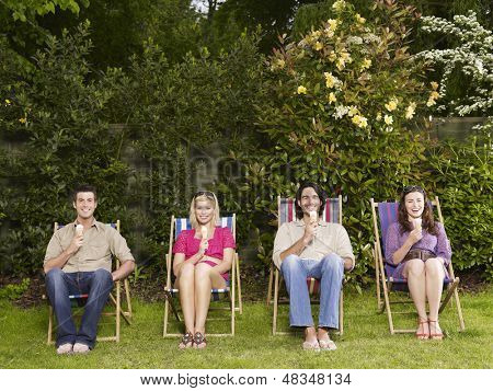 Full length group portrait of young people sitting in row with icecreams on deckchairs in garden
