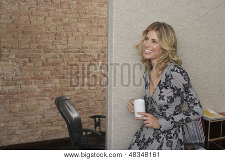 Side view of a smiling young woman leaning against bookcase with mug in office