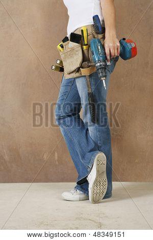 Lowsection-Seitenansicht einer Frau mit Toolbelt und Bohren an die Wand gelehnt