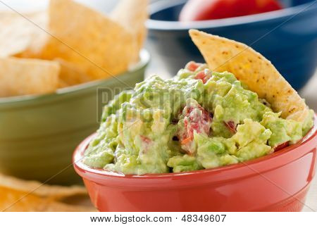 Guacamole and Chips - A studio shot of homemade guacamole in a red bowl., tortilla chips in a green bowl and a tomato in a blue bowl.